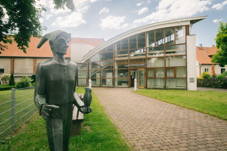 Der Eingang des Till Eulenspiegel-Museum in Schöppenstedt mit einer Bronzeplastik von Till Eulenspiegel, der eine Eule in der Hand hält.